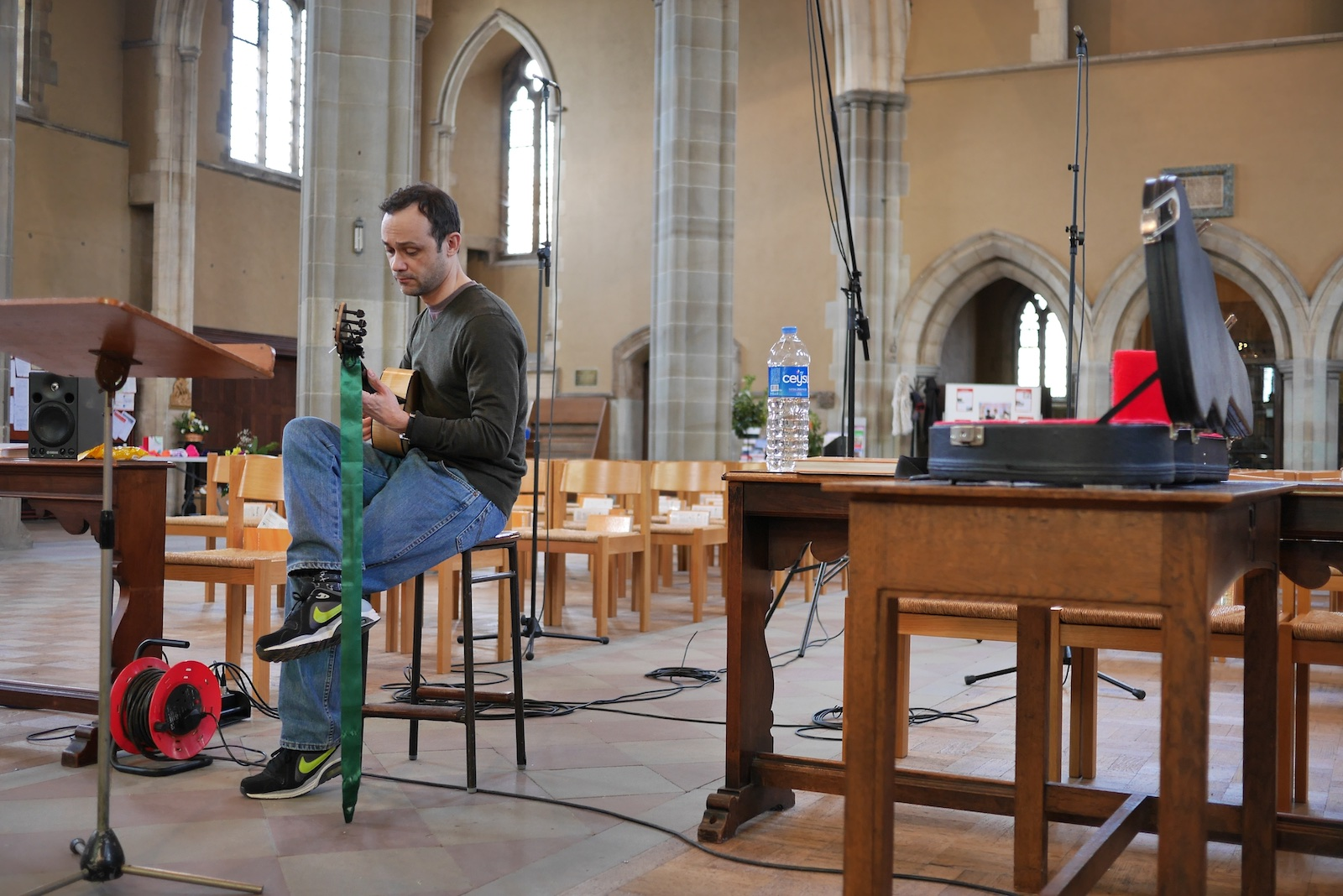 Eligio Quinteiro sitting alone in conducting position in the church, holding guitar
