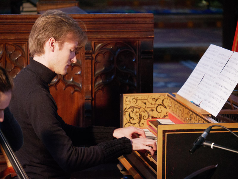 Nathaniel Mander with both hands at ornate harpsichord