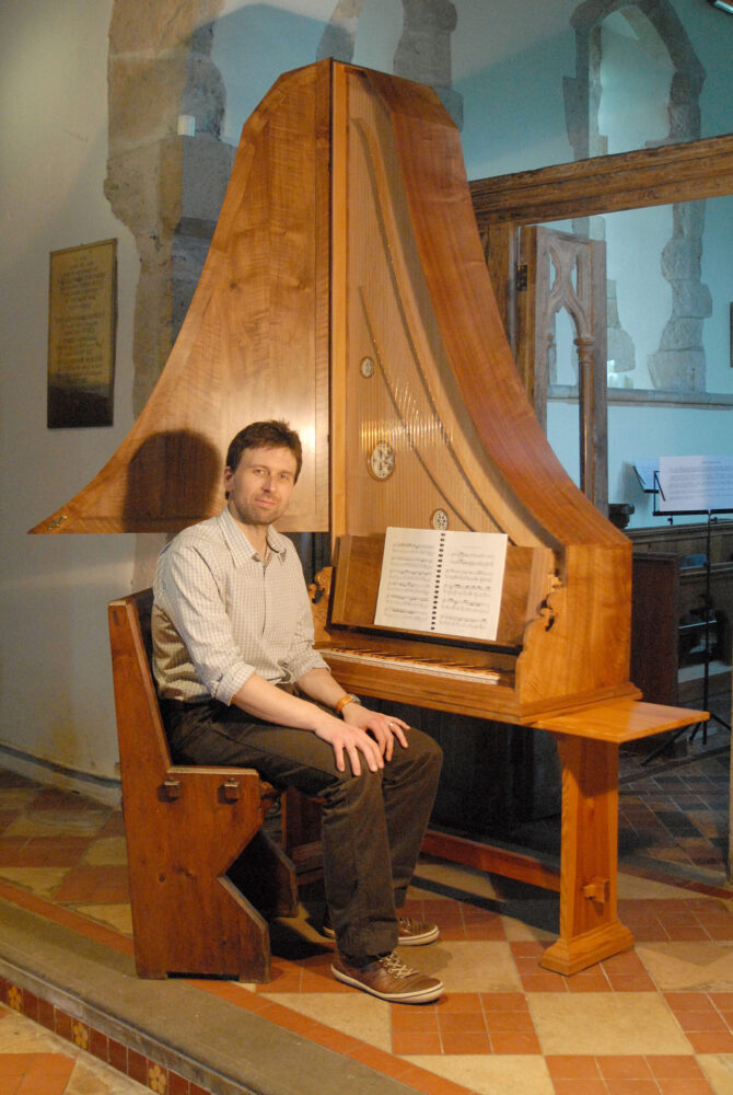 Robin Bigwood sitting at the clavicytherium in a church setting